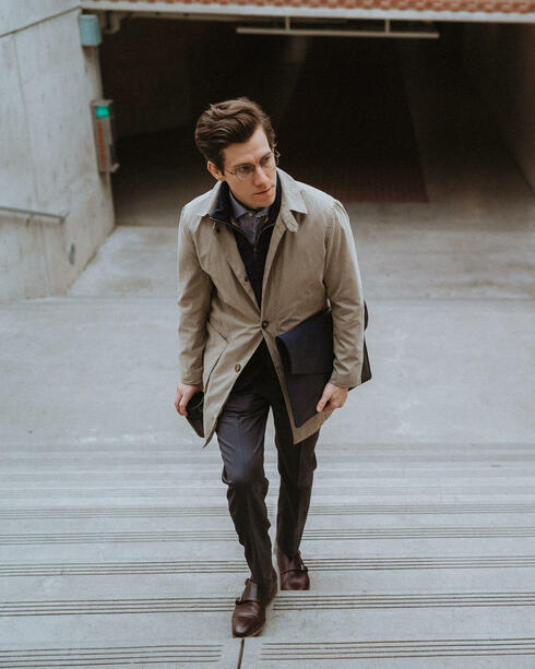 Tan raincoat with grey trousers